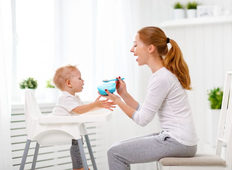 Mother feeds the baby from the spoon