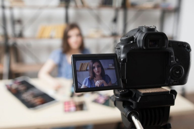 Young female beauty blogger on camera screen. Beautiful girl recording video at studio. Fashion, makeup, technology concept