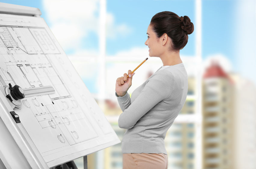 A woman looking at blueprints on a wooden table