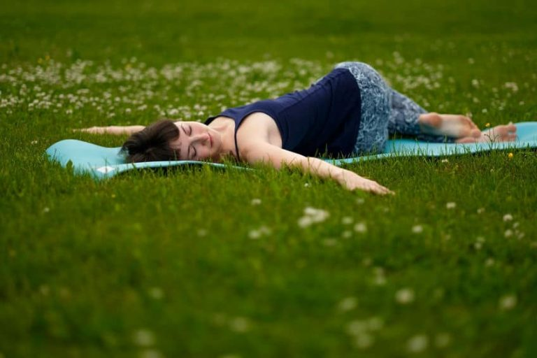 girl resting on a mat in the grass