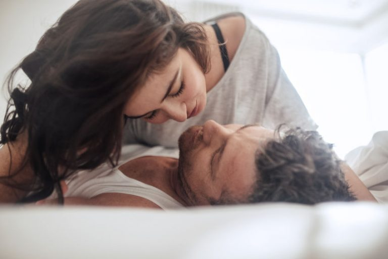 Young couple caressing lying in bed