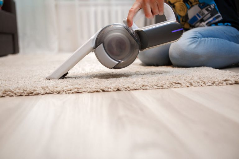 Woman cleaning of carpet in house portable rechargeable vacuum cleaner