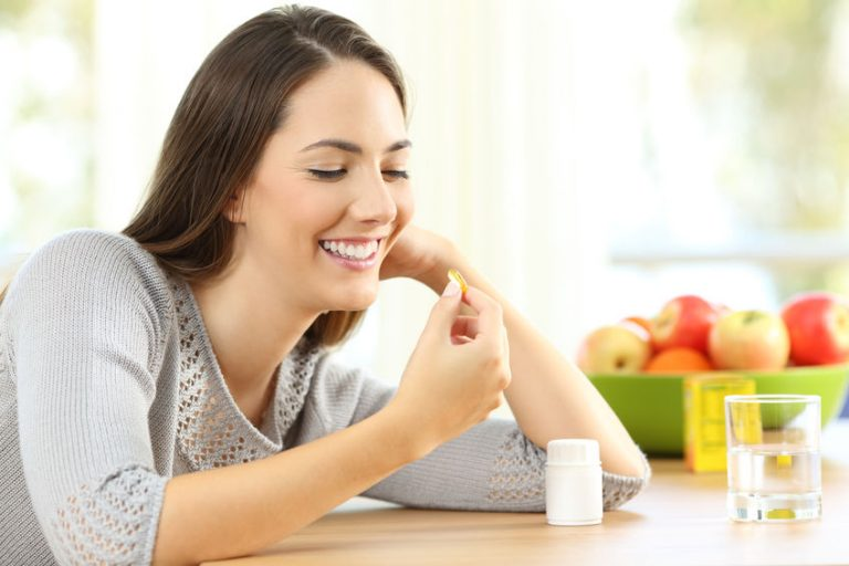 young woman taking magnesium citrate capsules