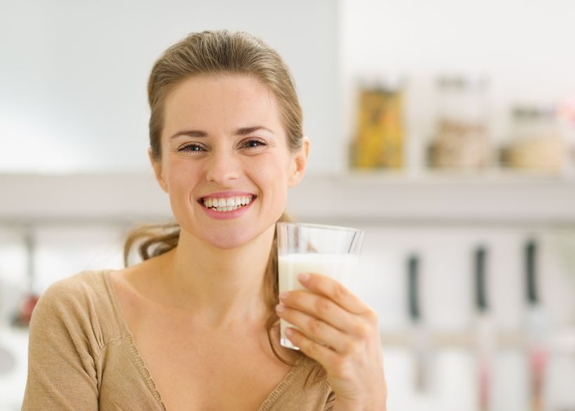 portrait of smiling young woman with glass of milk in kitchen