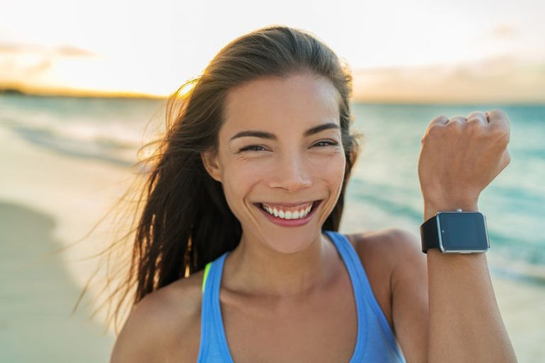 smartwatch happy girl showing display screen on trendy new smart watch fitness tracker wristwatch. healthy young asian sporty woman smiling on beach vacation running at sunset living an active life.