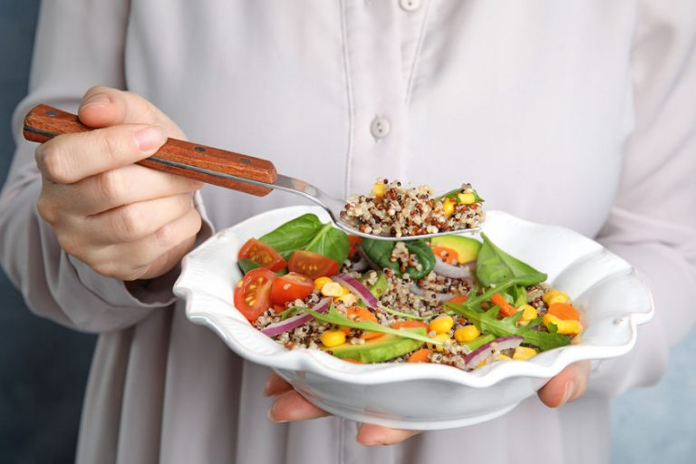 Woman eating healthy quinoa salad with vegetables from plate, closeup