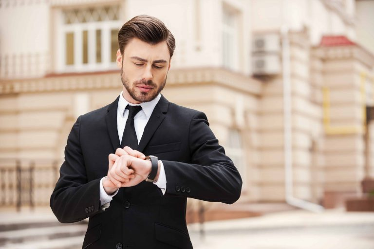 Handsome young man in formalwear looking at his watch