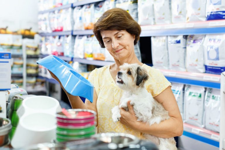 Smiling mature woman choosing pet food bowl for her puppy in pet supplies store