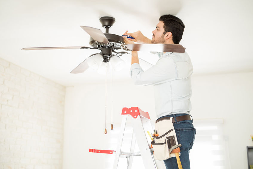 handyman stepping on a ladder and fixing a ceiling fan