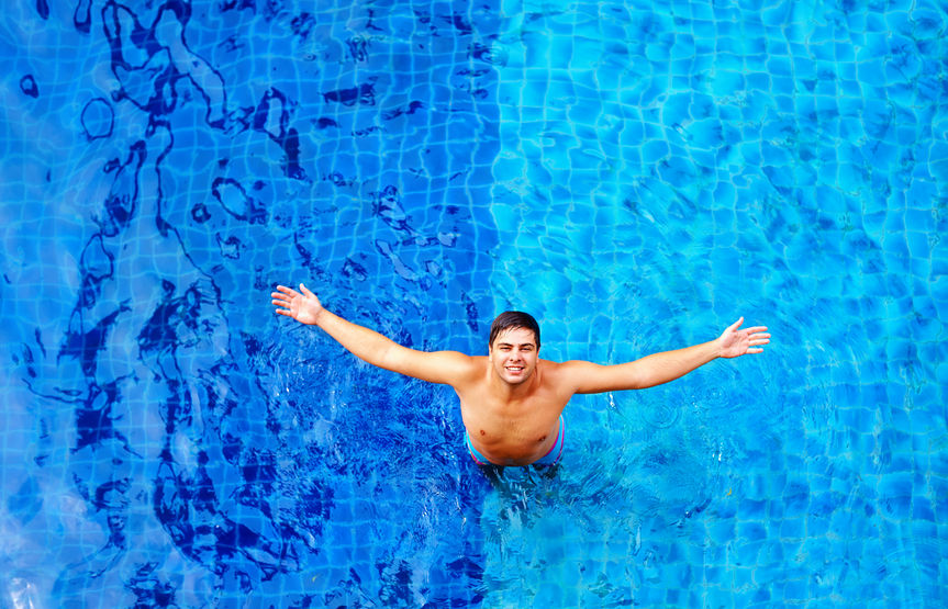 happy man enjoying vacation, while standing in pool water, top view