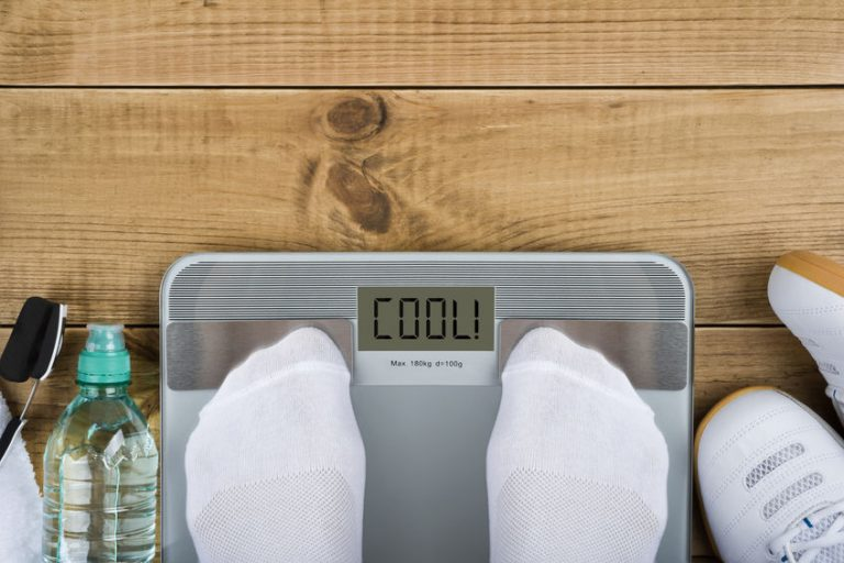 Weight loss concept with top view of weighting on scales