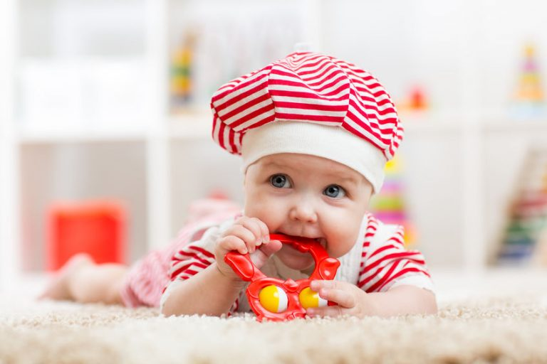 Child girl weared costue biting a toy lying on a carpet at home
