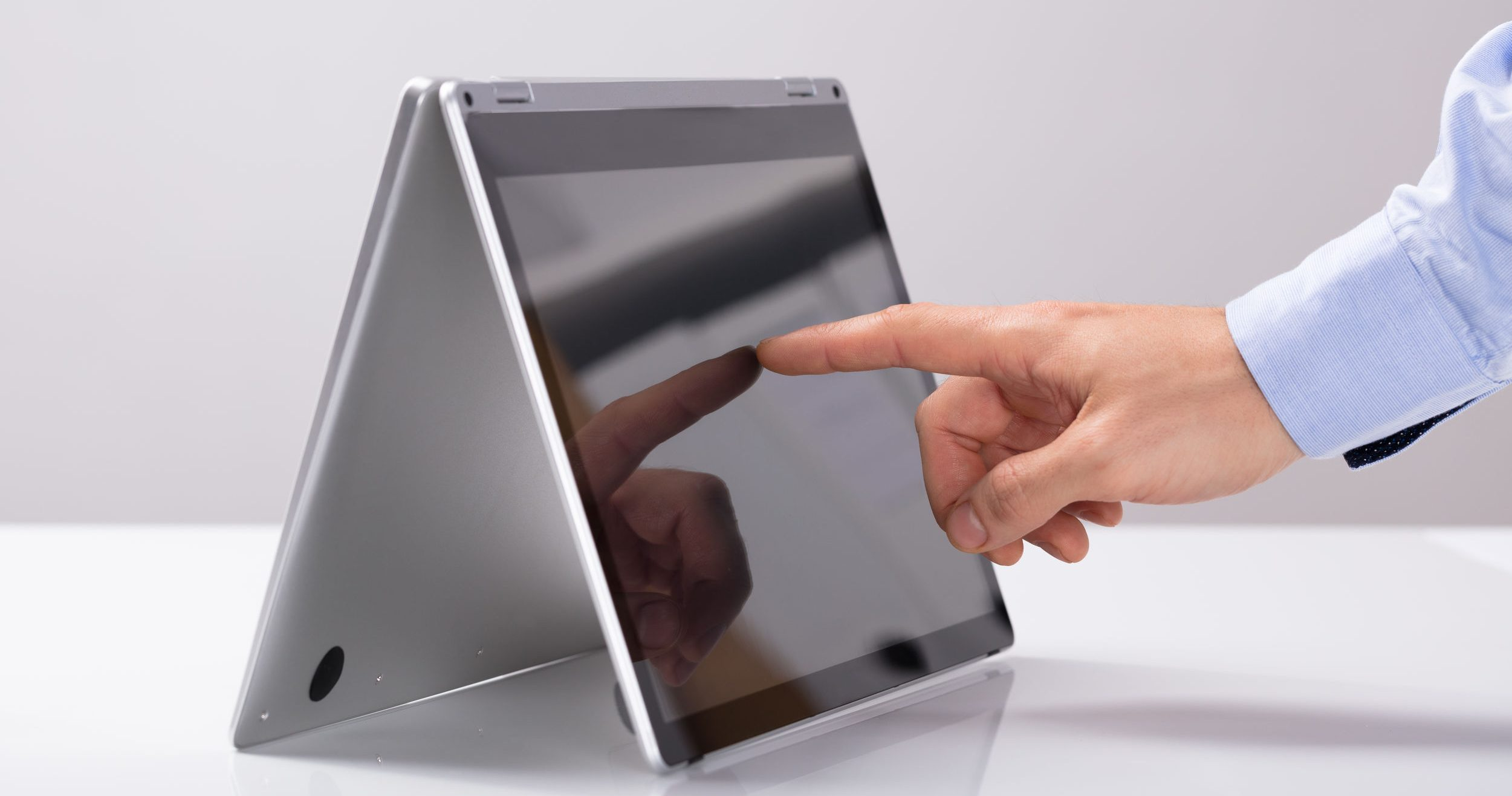 Businessman Touching His Finger On Hybrid Laptop Screen