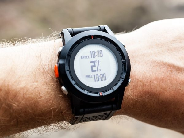 20439058 – runner on mountain trail looking at sportwatch
