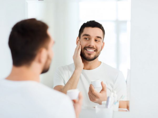 beauty, skin care and people concept – smiling young man applying cream to face and looking to mirror at home bathroom