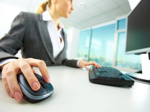 12872789 – image of female hands pushing keys of a computer mouse and keyboard