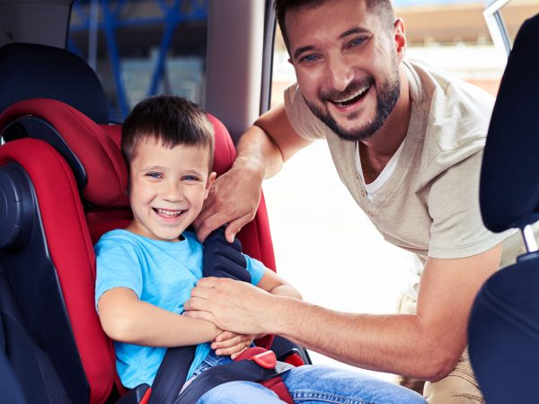 Close-up shot of happy father helping his son to fasten belt on car seat