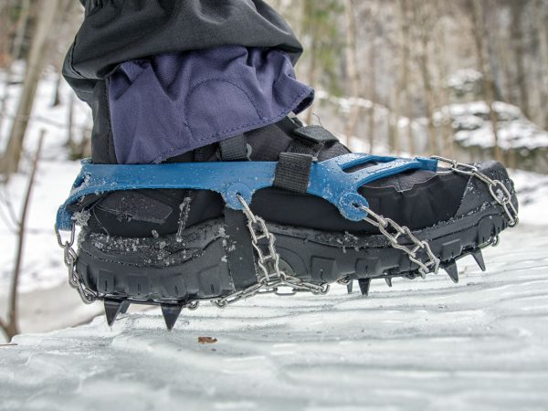 Crampons on black hiking boots on ice