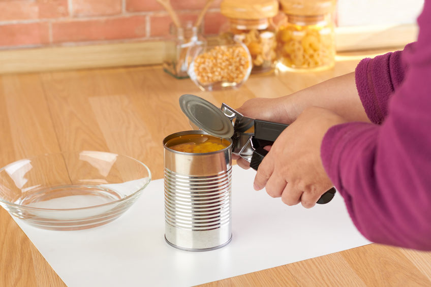 woman opening a can of corn with can opener