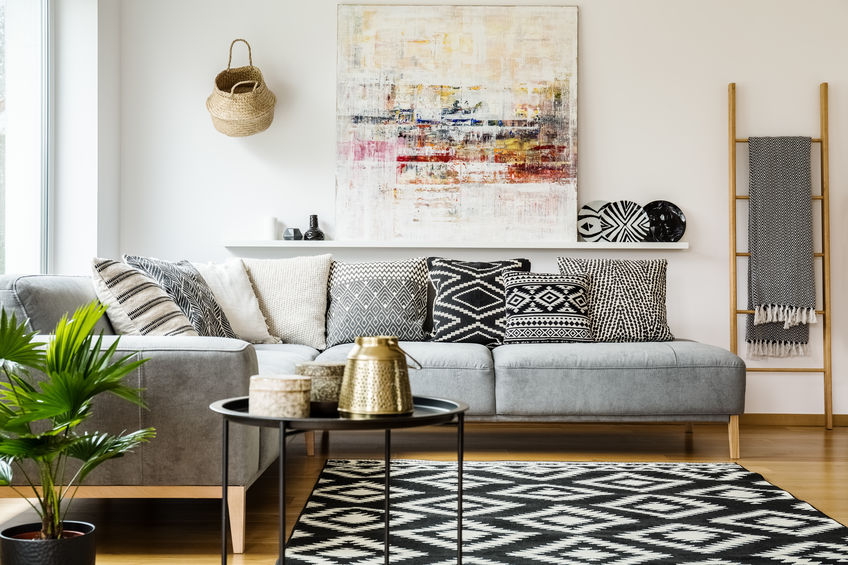 Patterned paillows on grey corner sofa in living room interior wi