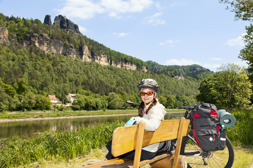 Portrait of woman cyclist resting on a bench in nature.