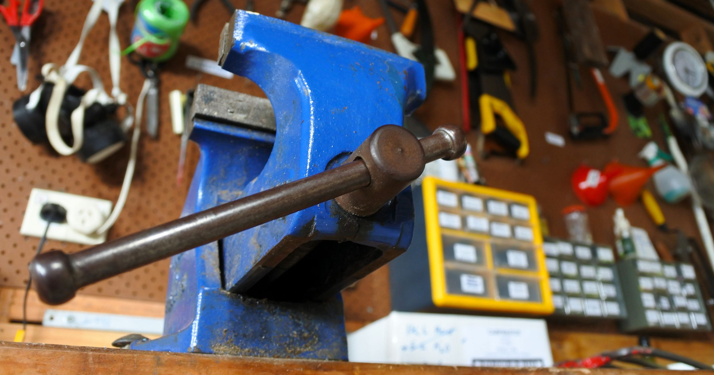 A blue vise in aworkshop, a mechanical apparatus used to secure an object to allow work to be performed on it.