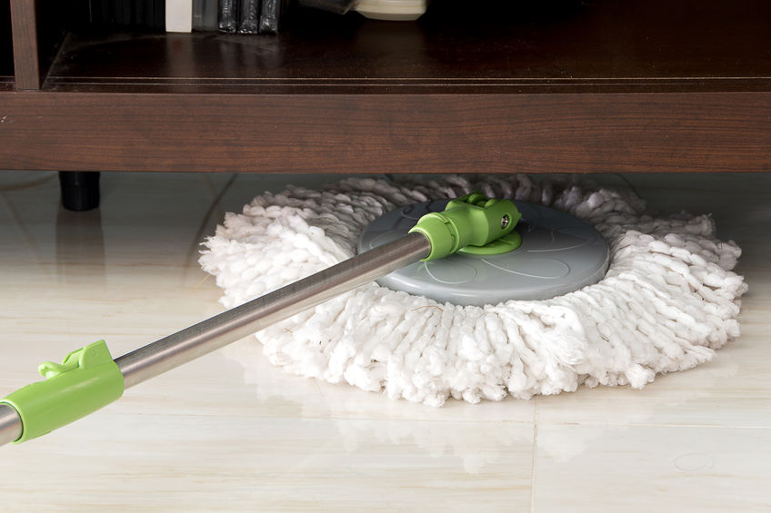cleaning floor with mop under Shelves