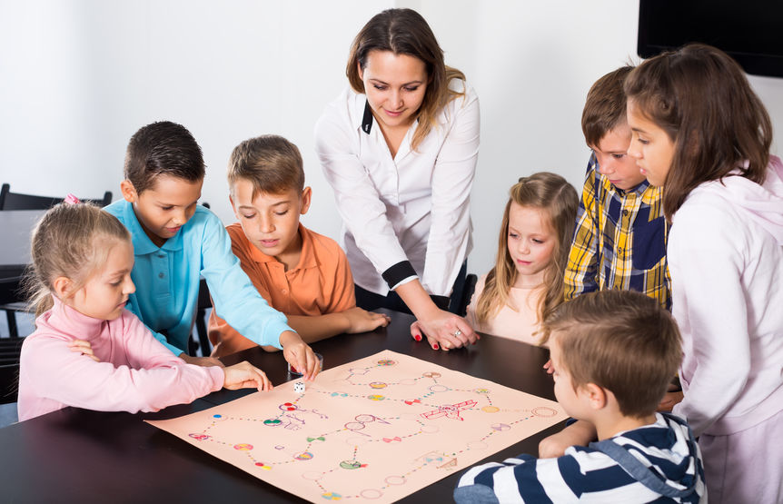 Children sitting at table with board game and dice in school