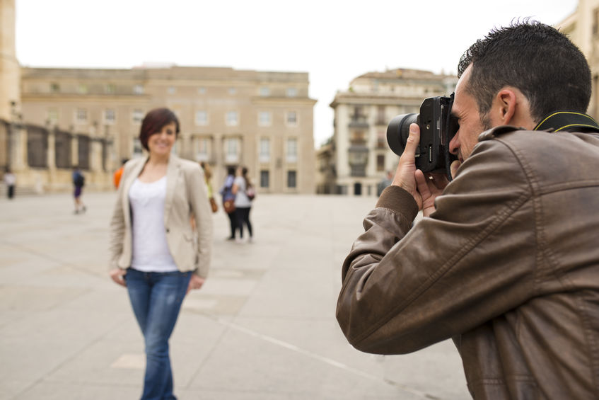 Man taking picture of attractive woman in public place