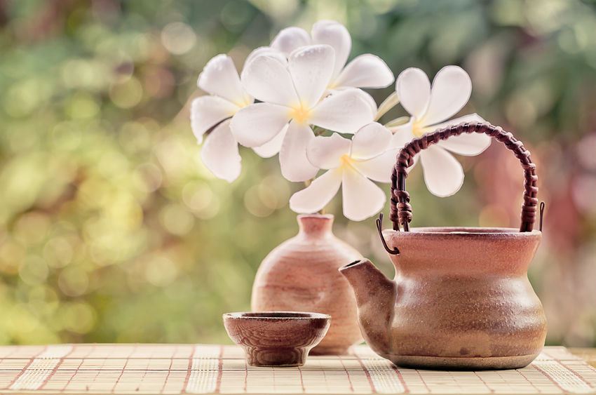 Soft focus and blurred teacup and teapot with vase of plumeria