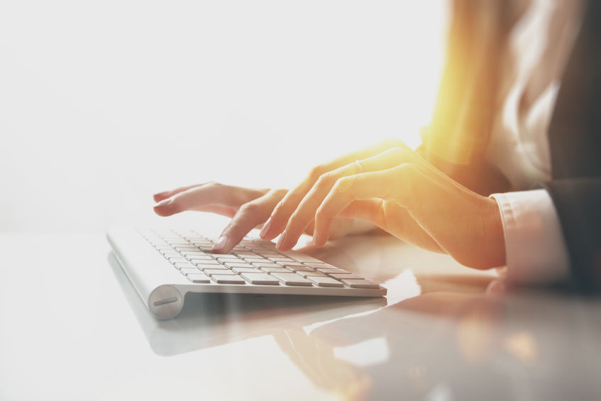 Closeup photo of female hands typing text on a wireless keyboard. Business woman working at the office. Visual effects, white background