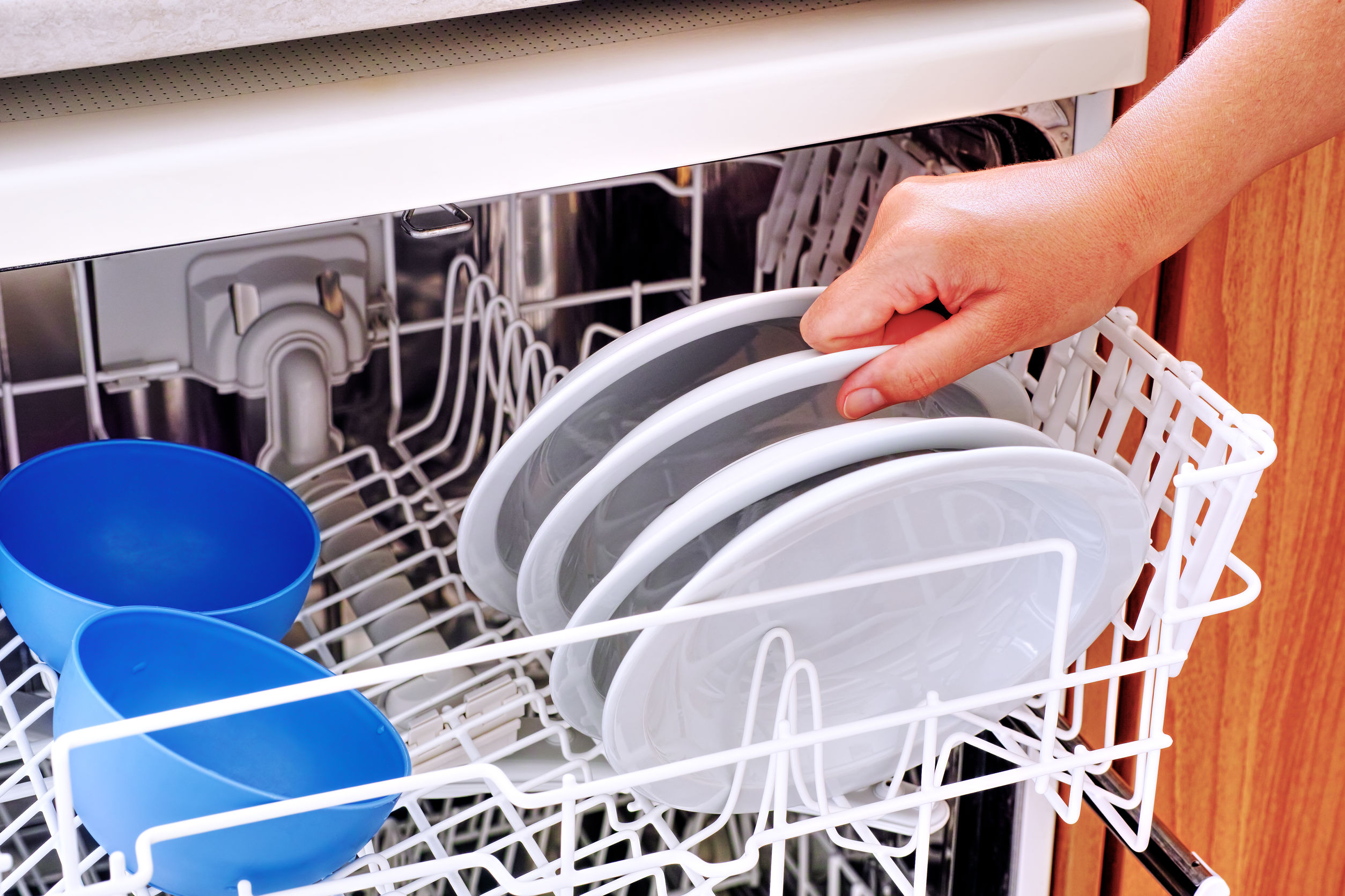 Woman hand take plate from dishwasher