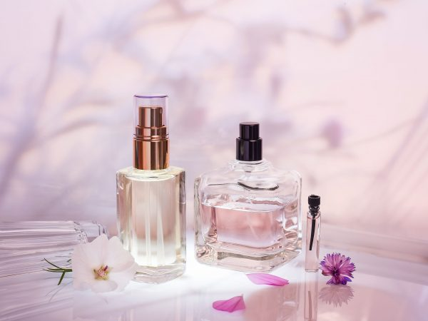 Perfume bottle on a light pink floral background. Selective focus. Perfumery collection, cosmetics.