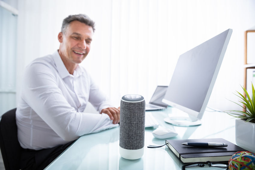 Man Listening To Wireless Speaker In Office