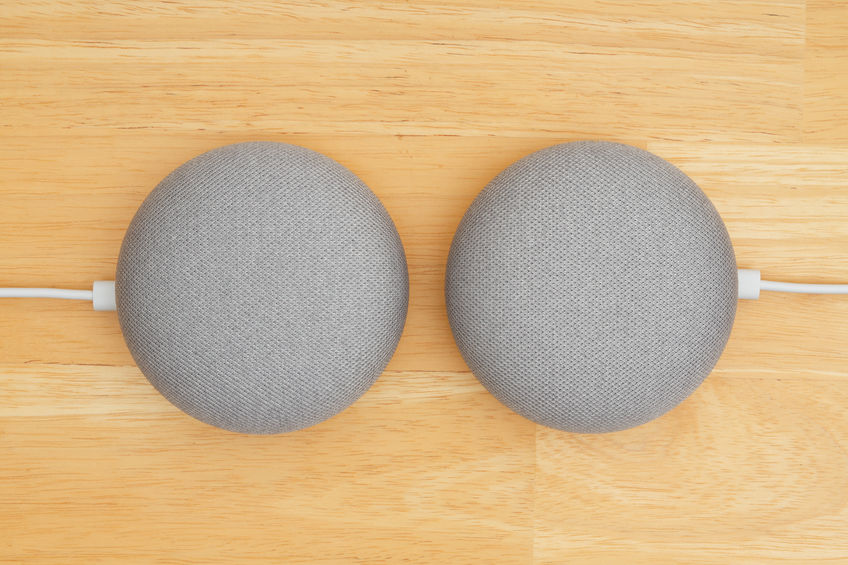 Two Google home devices on a wood desk