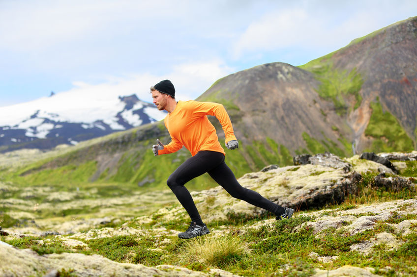 running man in cross country trail run. fit male runner sport training outdoors in beautiful mountain nature landscape with snaefellsjokull, snaefellsnes, iceland.