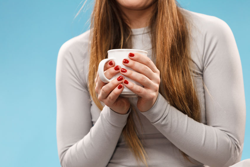 Woman in winter gray sports thermal underwear for skiing training holds mug with tea or coffee warming herself studio shot on blue.