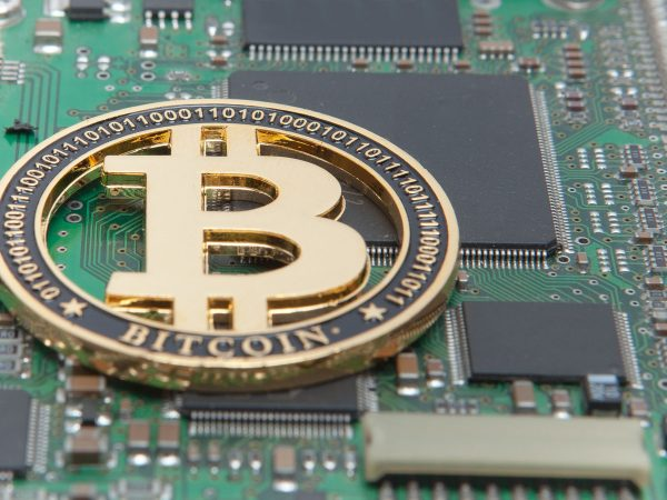 Close-up of gold bit coin, computer circuit board with bitcoin processor and microchips. Electronic currency, internet finance rypto currency. Bitcoin mining.