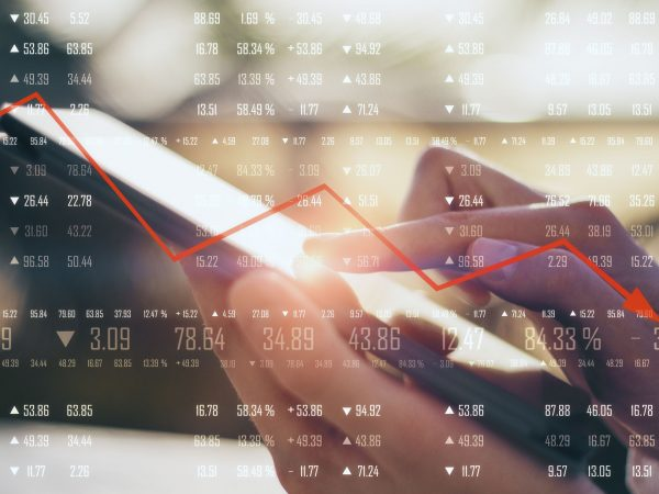Close up of hand using tablet with financial digits and downward red arrow on blurry background. Economic decline concept. Multiexposure