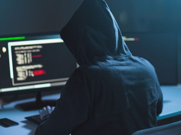 cybercrime, hacking and technology concept – male hacker in dark room writing code or using computer virus program for cyber attack