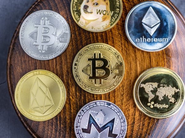 Different cryptocurrencies over gavel wooden board.Concept image for cryptocurrency