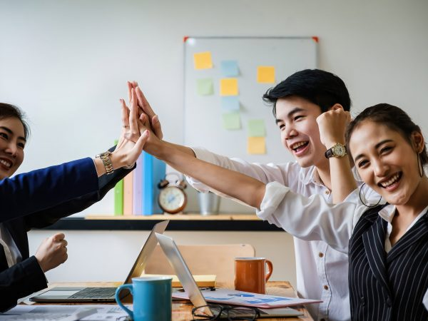 Business team giving a high fives gesture as they laugh and cheer their success. Achievement and Business Goal Success Concept. soft focus